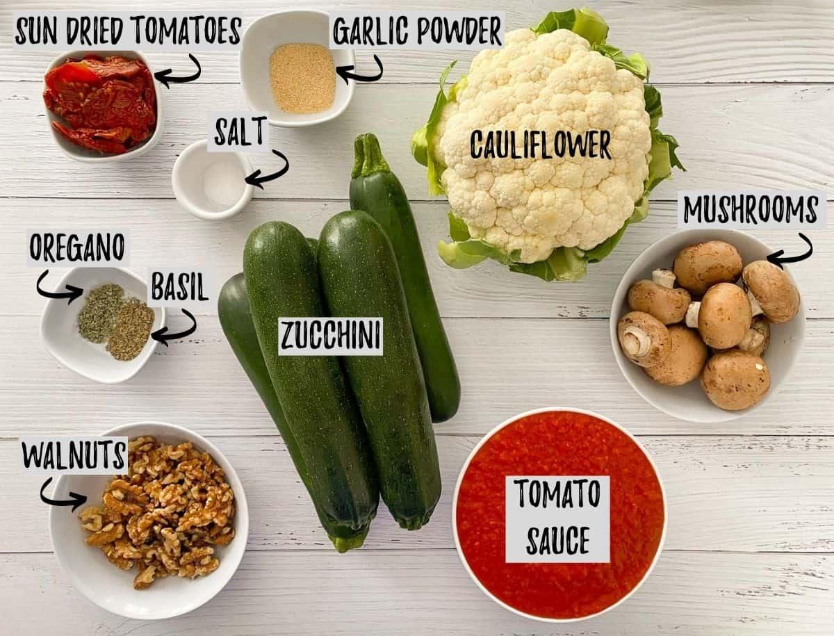 Ingredients to make vegan zoodles on white deck.