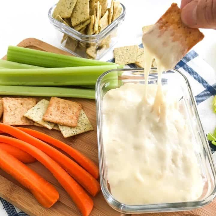 Cracker being dipped into bowl of cheese dip with veggies scattered around it.