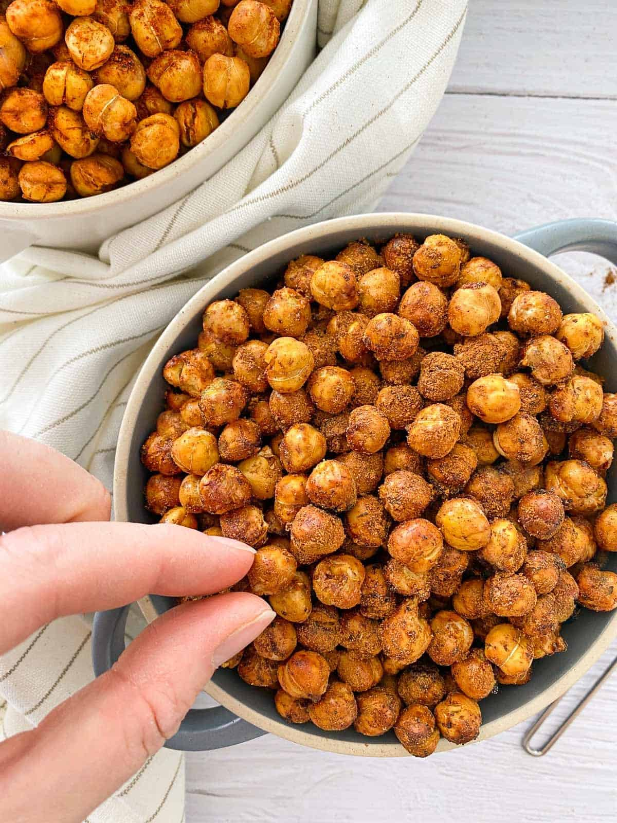Fingers grabbing a chickpea from bowl of air fried chickpeas.