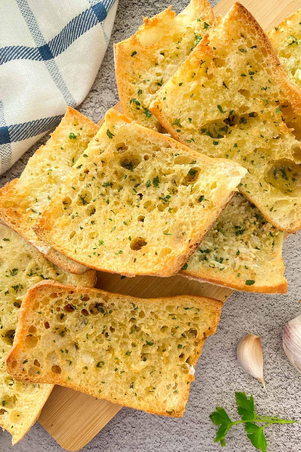 Crunchy garlic bread on cutting board with parsley garnish.