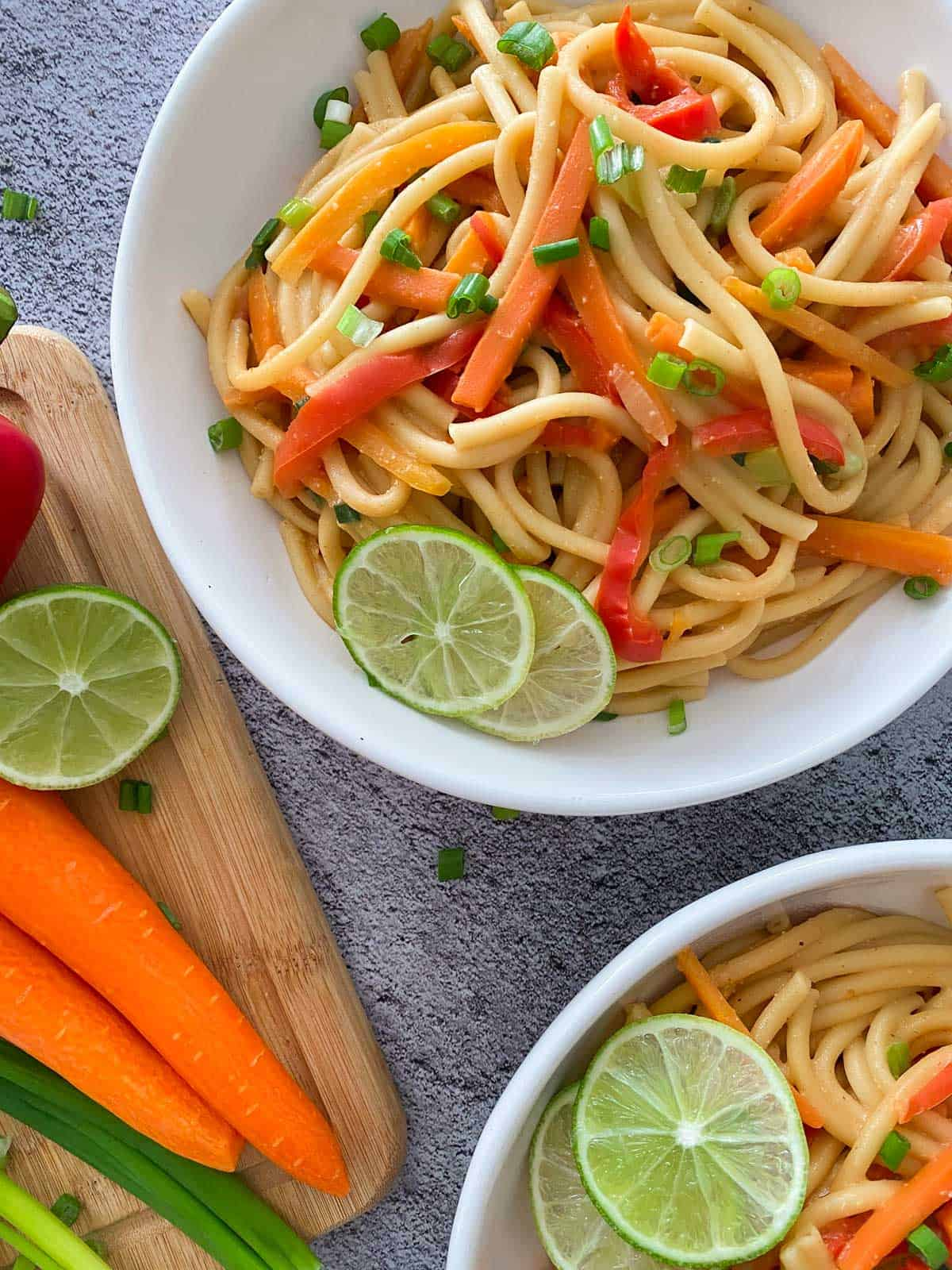 Plate of Thai noodles with carrots and lime on cutting board, beside it.