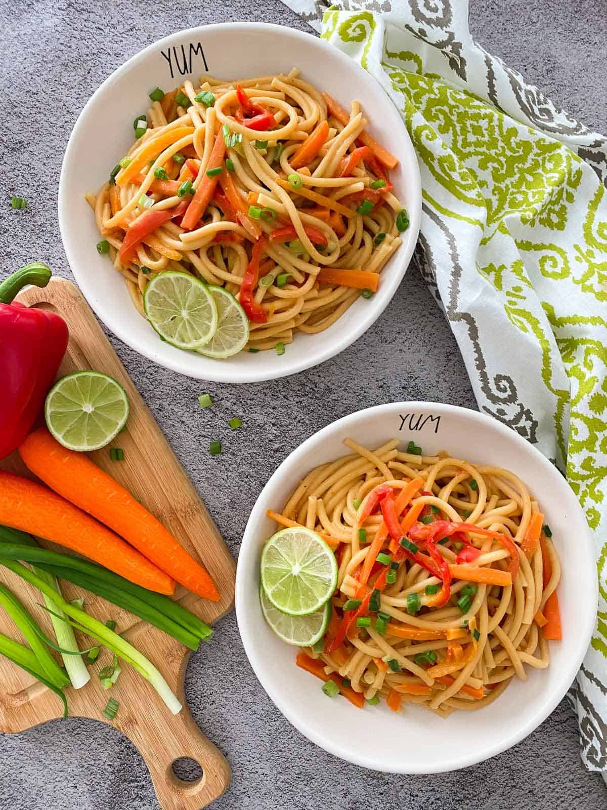 Two bowls of thai peanut noodles with lime and green onion garnish.