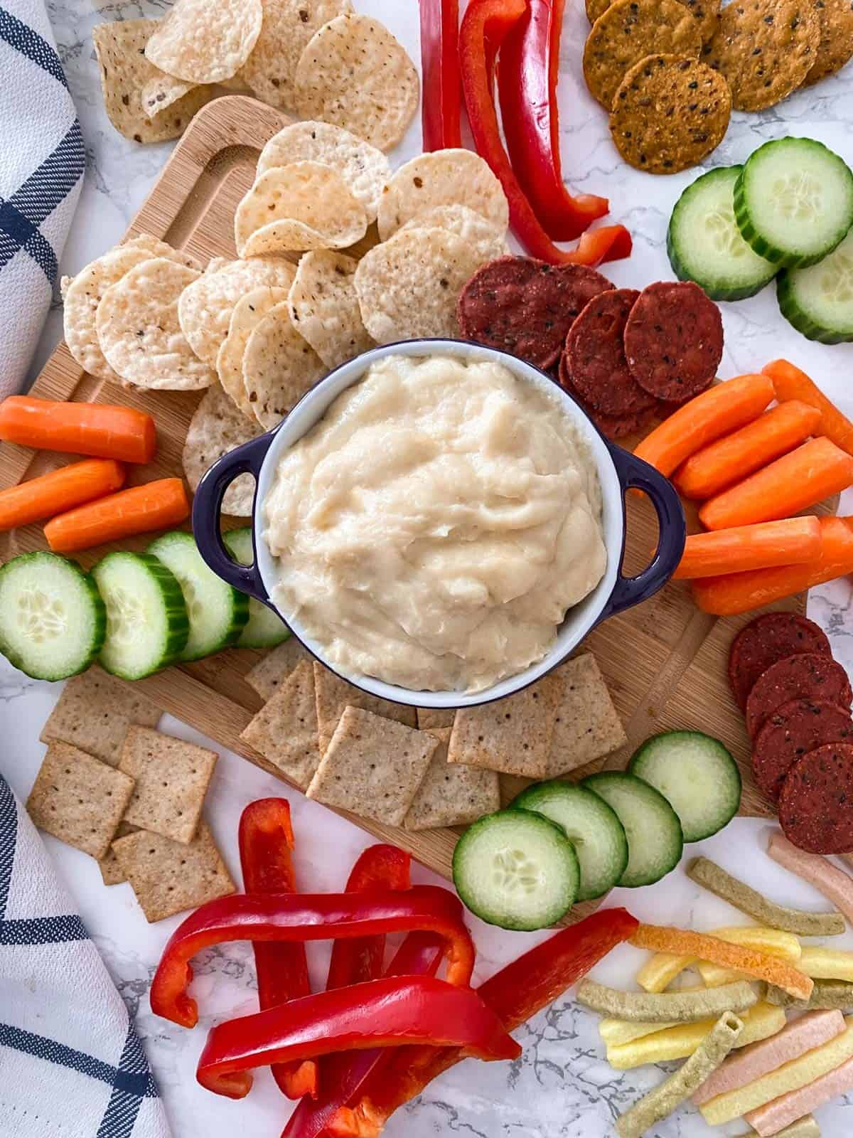 Bowl of cheese dip with chips, crackers and veggies scattered around it.