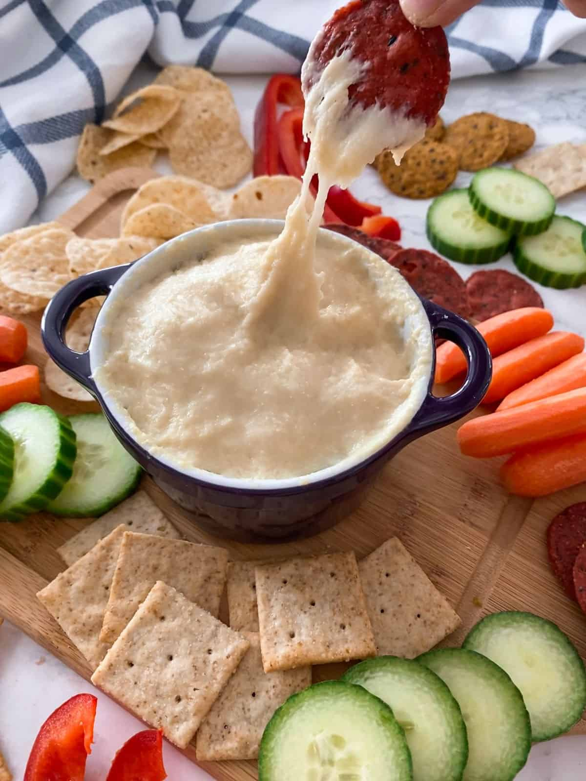 Cracker dipped in cheese dip being lifted from bowl.