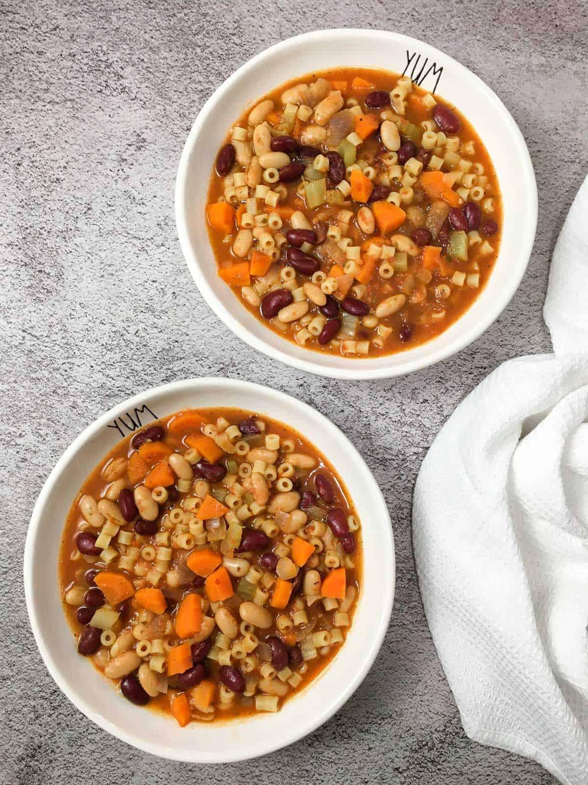 Two bowls of vegan pasta e fagioli on concrete surface.