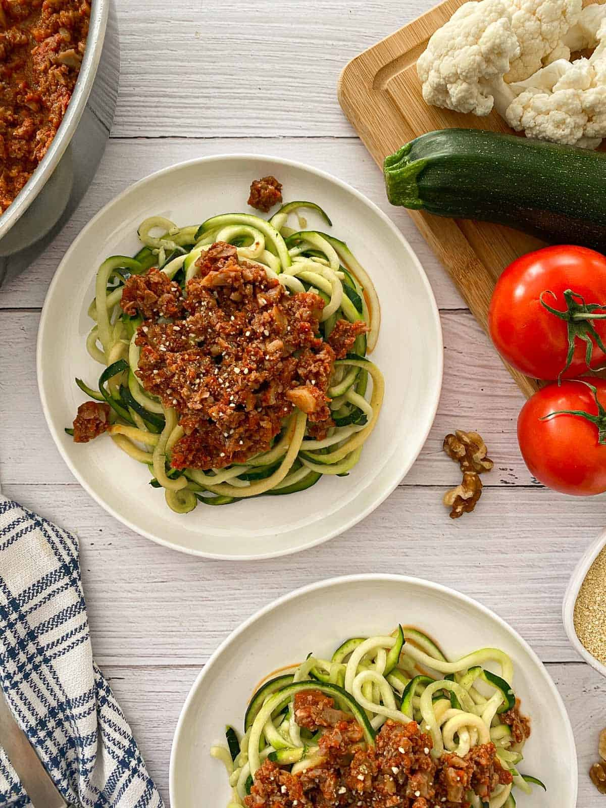 Zucchini pasta with vegan bolognese sauce on top and tomatoes and zucchini on the side.