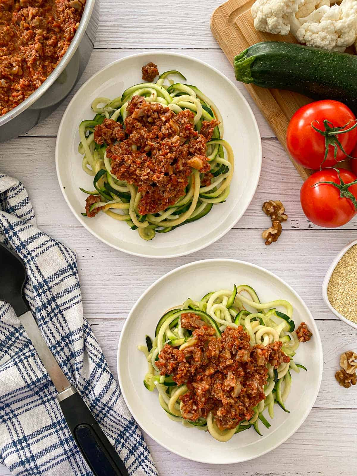 Two plates of zoodles with vegan bolognese sauce on top.