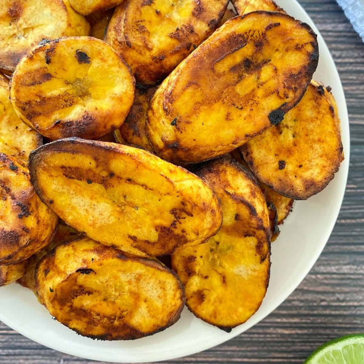 White plate with air fried plantain chips inside.