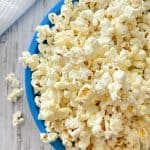 Blue bowl overfilled with popcorn that's spilling over the sides.