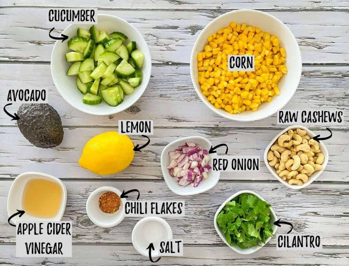 Ingredients needed to make vegan elote in bowls on grey deck.