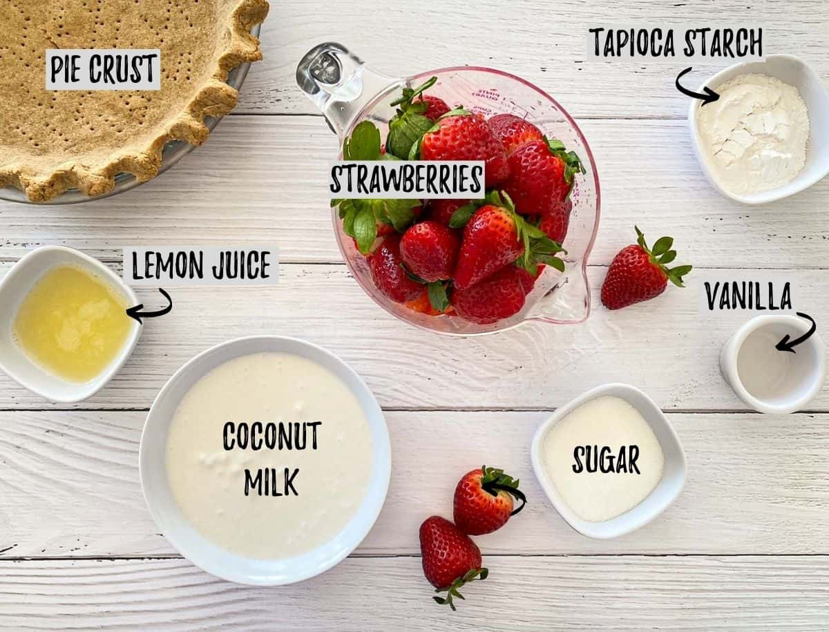 Ingredients needed to make strawberry pie scattered on deck.