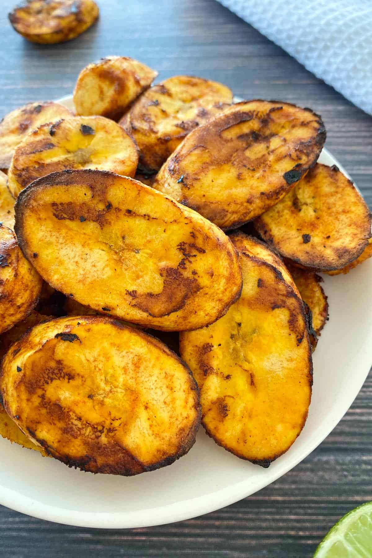 Plantain slices that have been air fried piled onto small white plate.