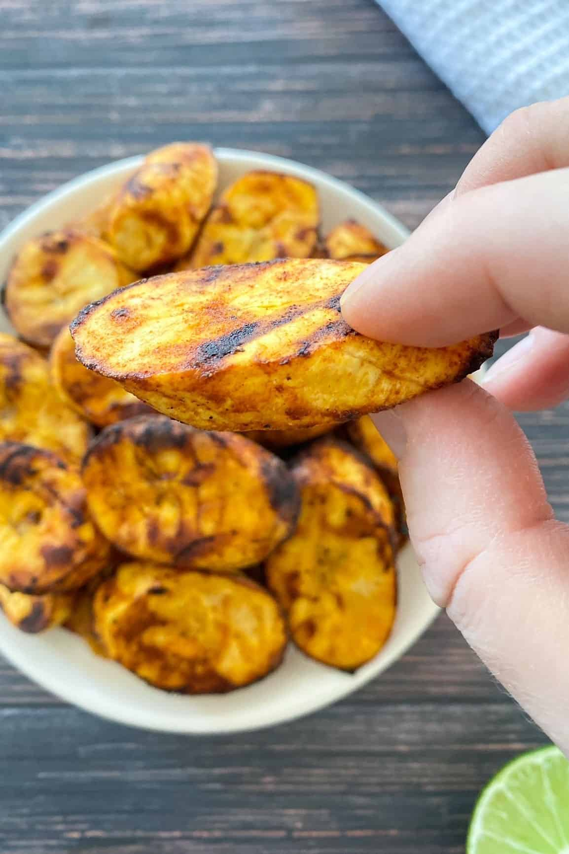 Hand holding up slice of air fried plantain over plate with additional slices.