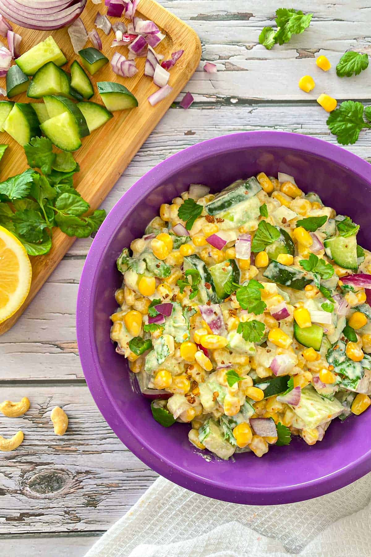 Bowl filled with vegan elote salad with cashews, corn and cilantro scattered around.