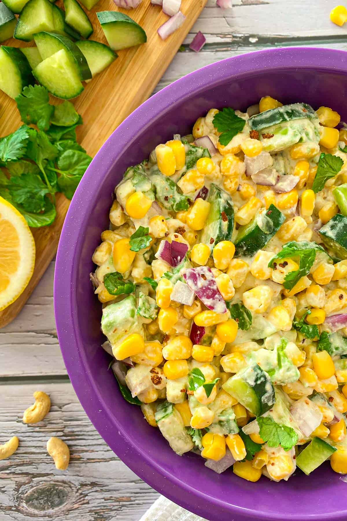 Purple bowl with creamy corn salad and red onion and cilantro on top.
