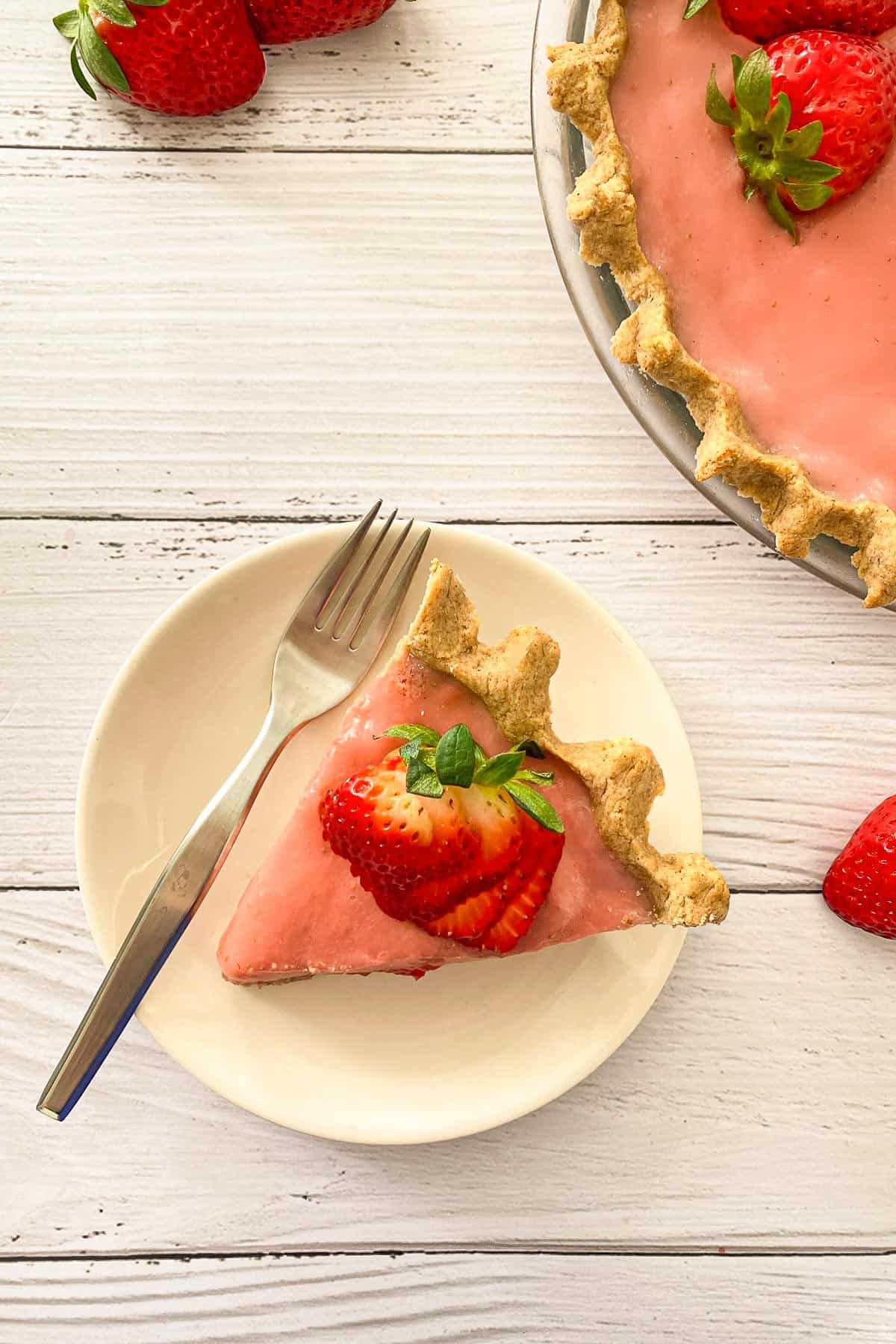 Overhead view of slice of pie in plate with strawberry slices on top.