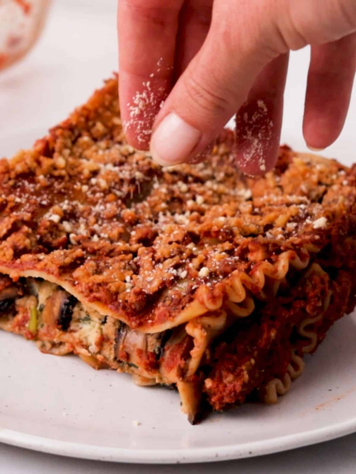 Hand sprinkling parmesan cheese on slice of vegan lasagna.
