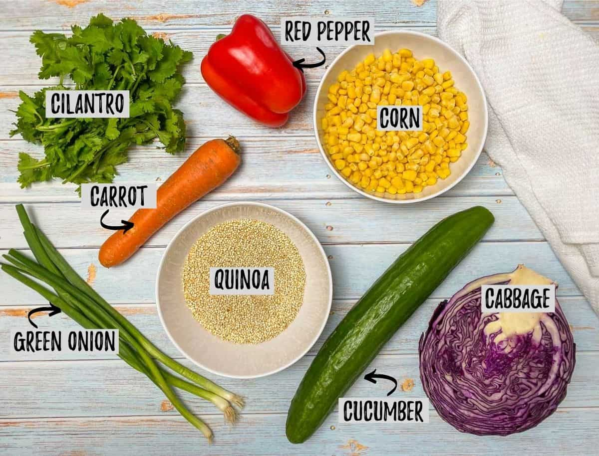 Bowl of corn and raw quinoa with a cucumber, carrot, red pepper and purple cabbage around it.