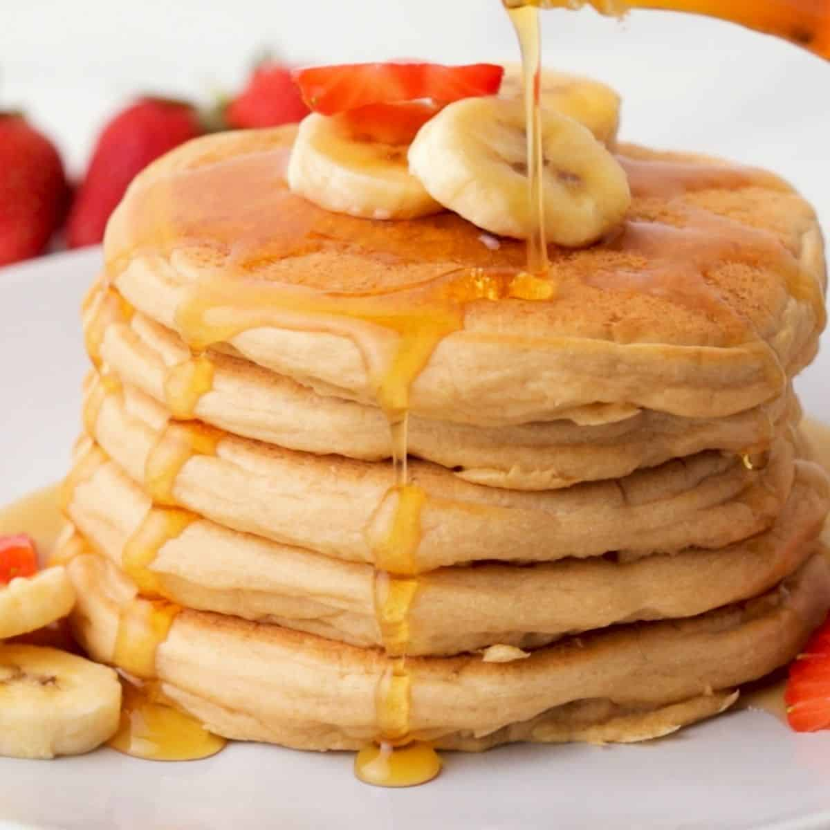 stack of vegan pancakes with banana slices on top and syrup dripping down.