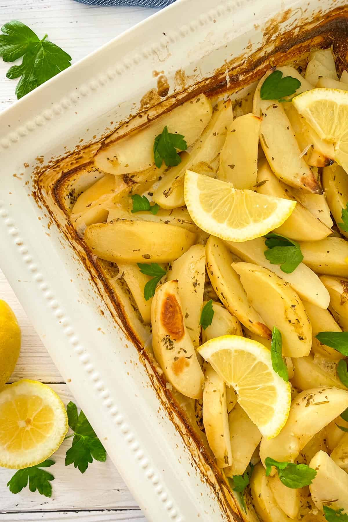 Roasted potatoes in white tray with lemon wedges and parsley garnish.