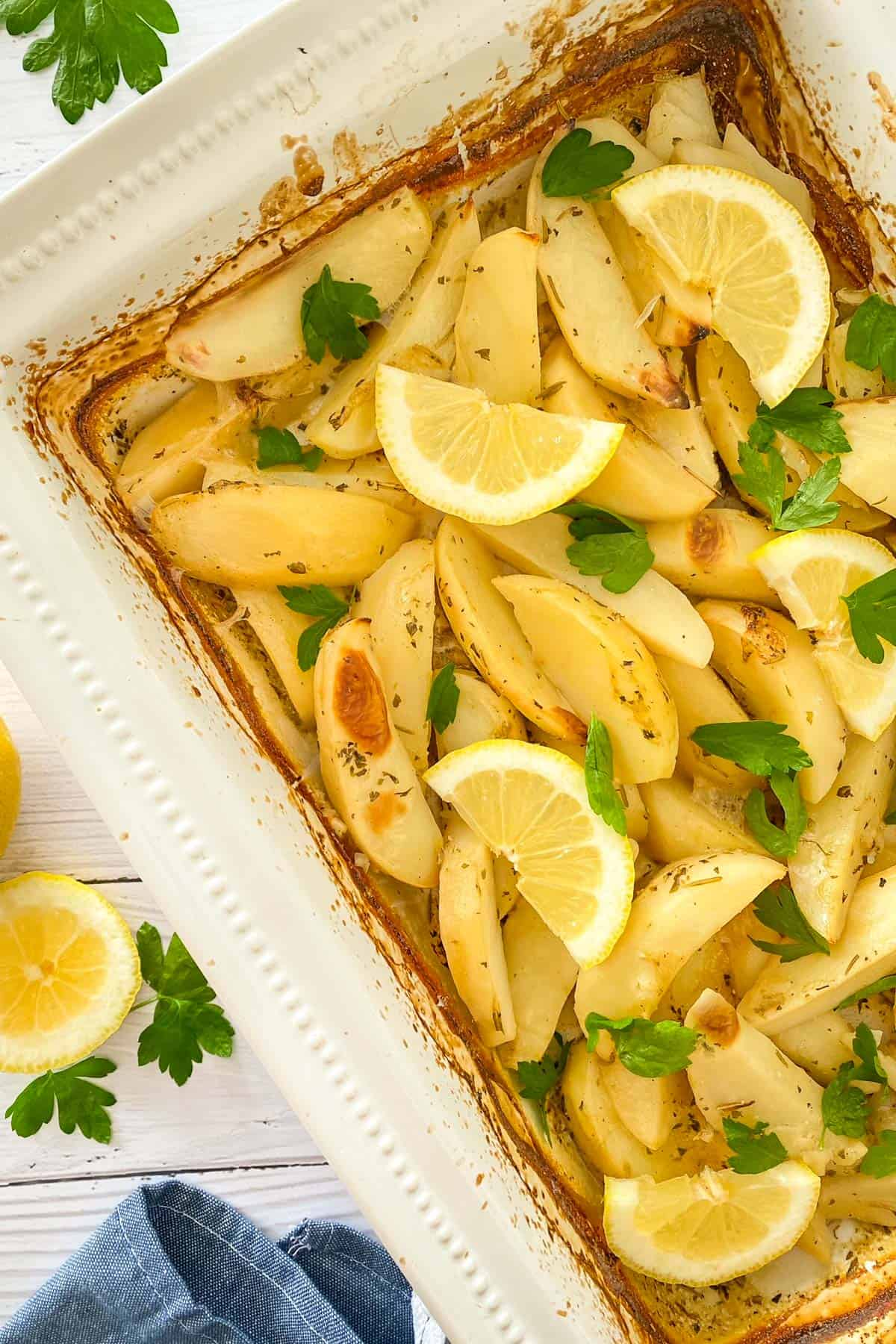 White baking dish filled with roasted potatoes with lemon wedges and parsley on top.