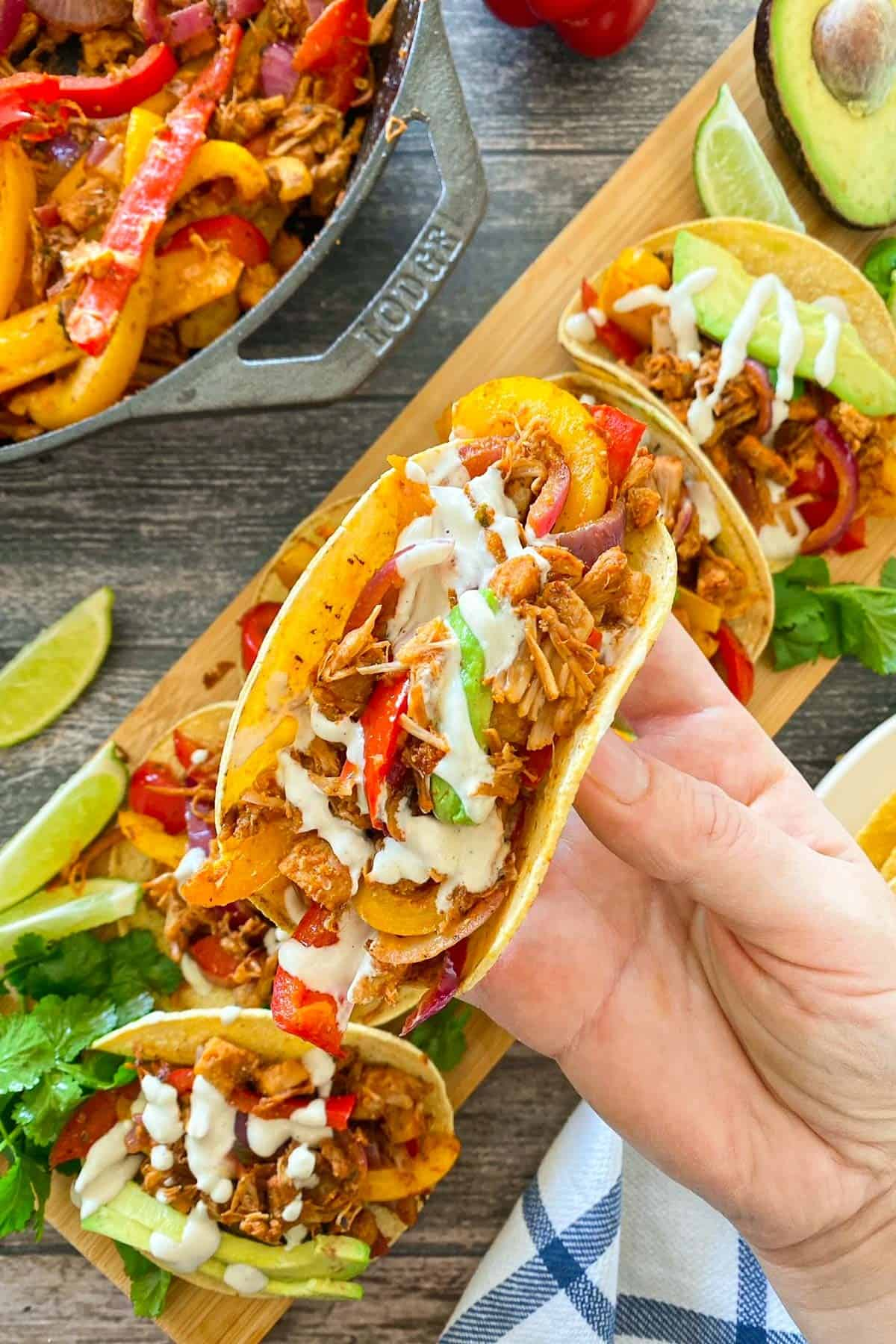 Hand holding up jackfruit fajita with more of them below on cutting board.