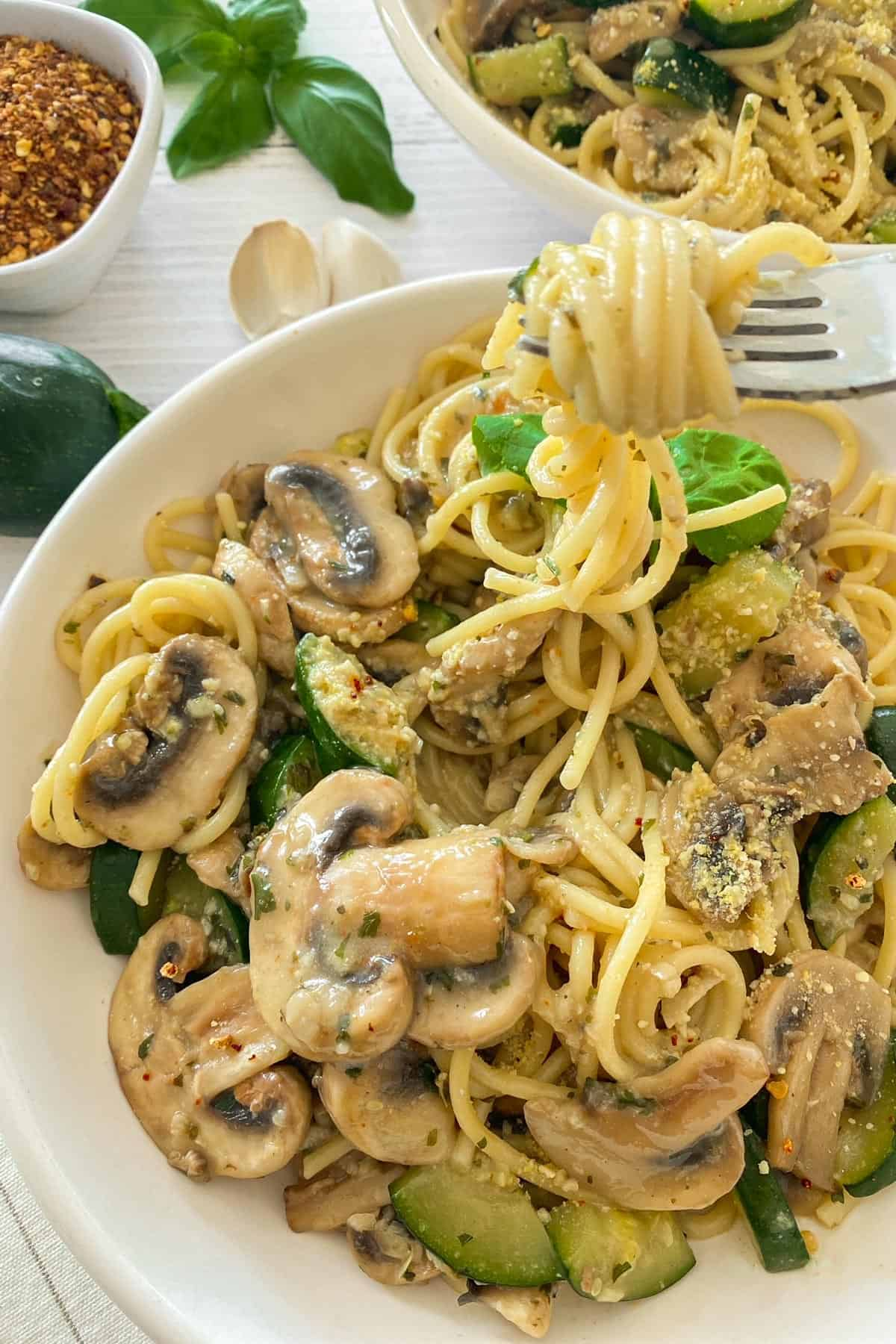 Plate of spaghetti with mushrooms and zucchini with a bite twirled around fork.