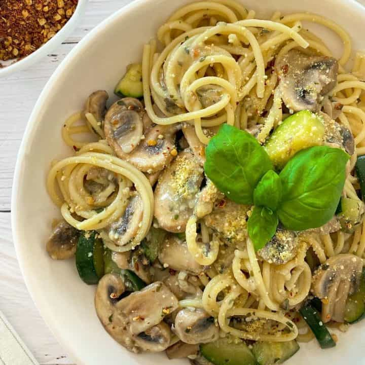 Plate of spaghetti, zucchini and mushrooms with basil on top.