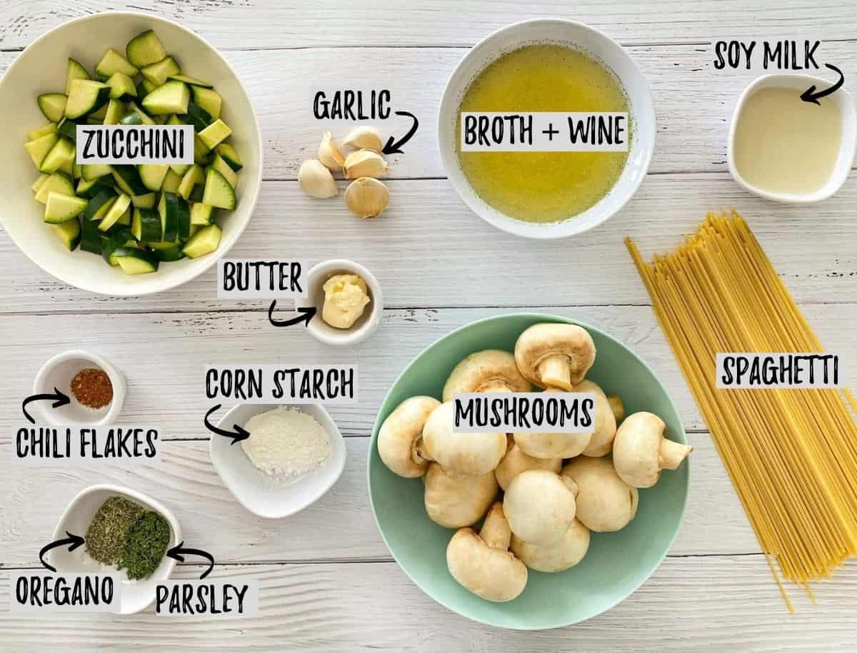 Ingredients to make mushroom zucchini pasta on white deck.