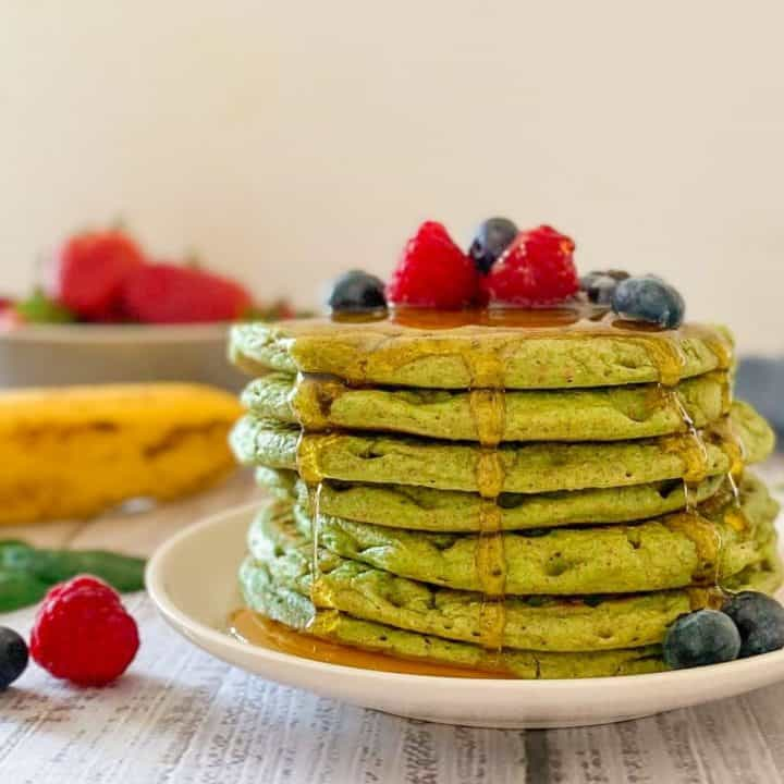 Stack of green pancakes on plate with berries on top.
