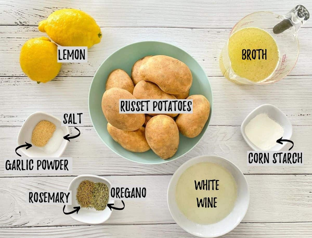 Bowls of potatoes, lemons, broth and seasoning on white deck.
