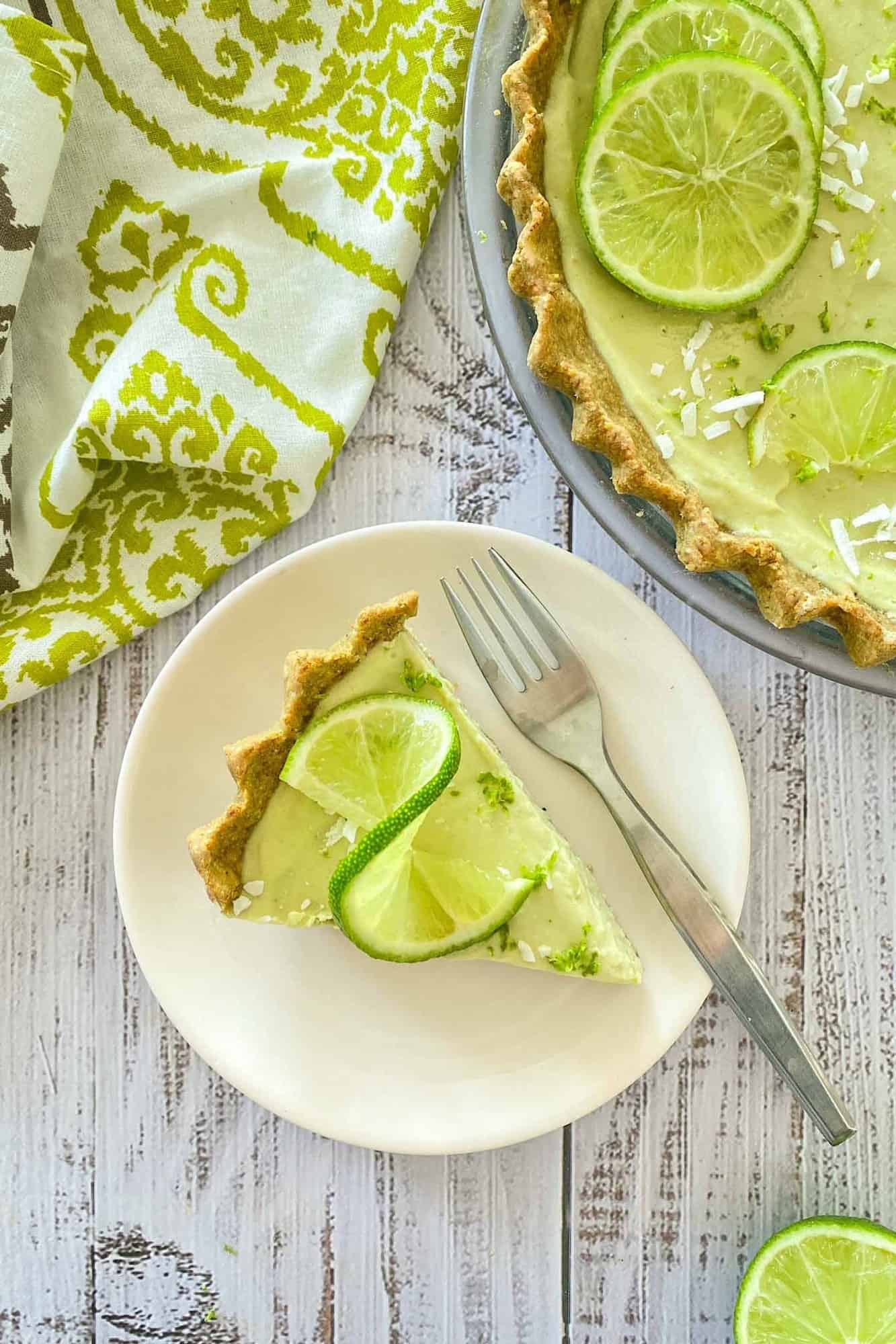 Overheat view of pie slice with lime garnish on white plate with fork beside it.