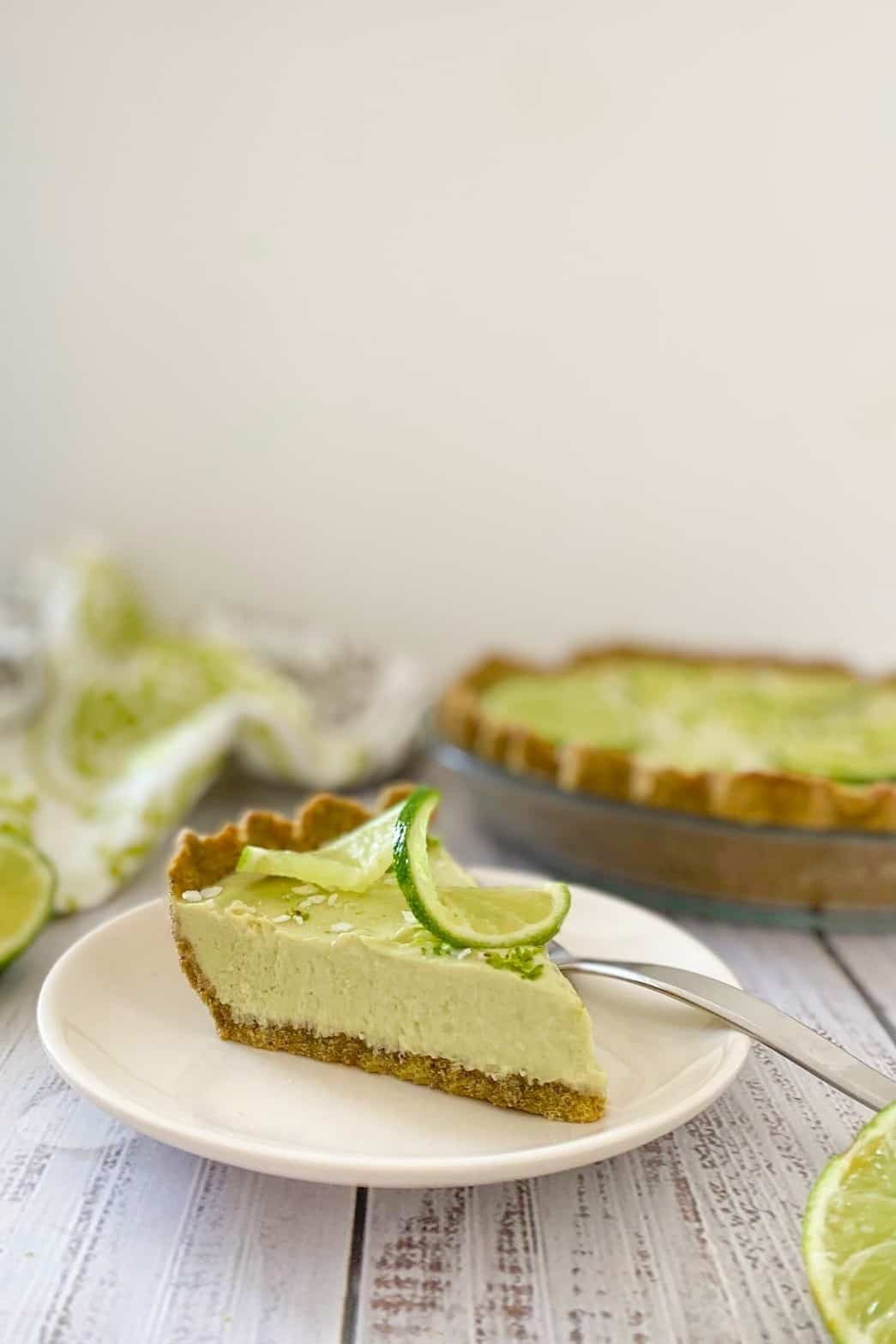 Side view of slice of lime pie with remaining pie in background.