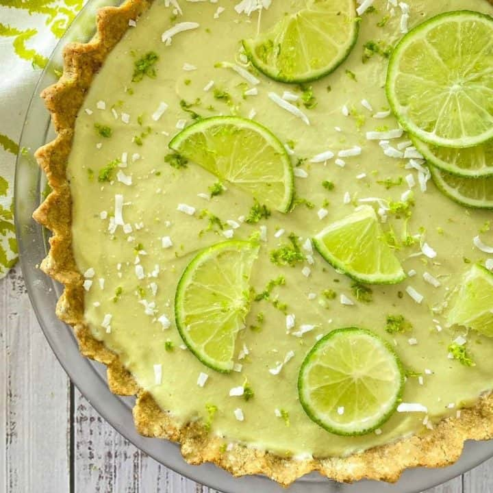 Overhead view of key lime pie with lime zest and coconut shreds on top.
