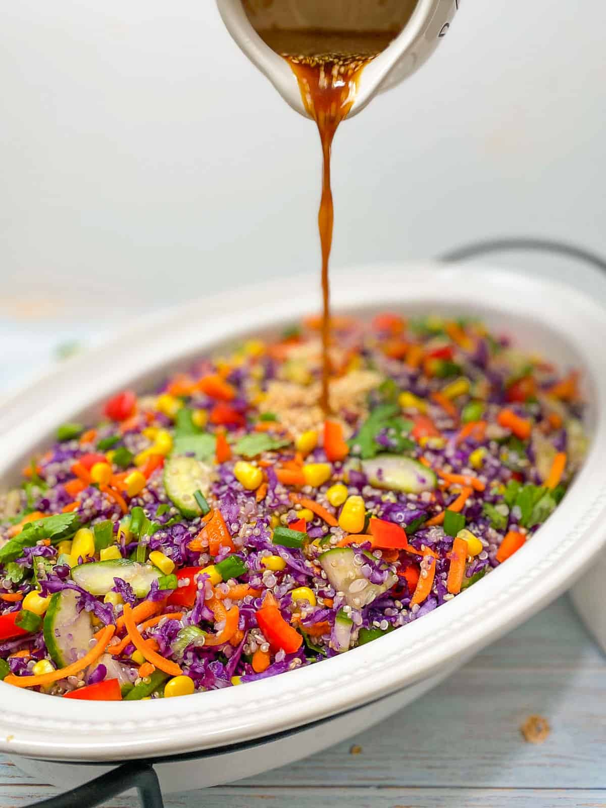 Salad dressing being poured on top of cabbage salad