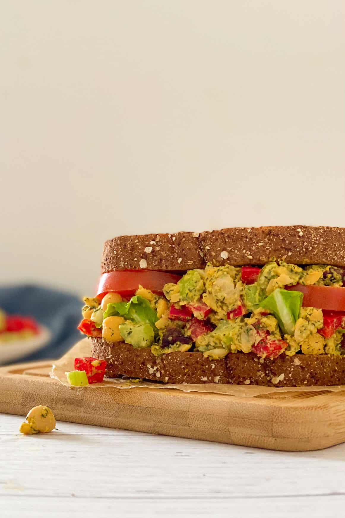 Chickpea salad sandwich on cutting board with chickpeas and pepper falling out.