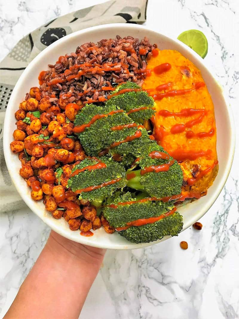 Bowl with chickpeas, broccoli, rice, sweet potato and hot sauce drizzled on top.