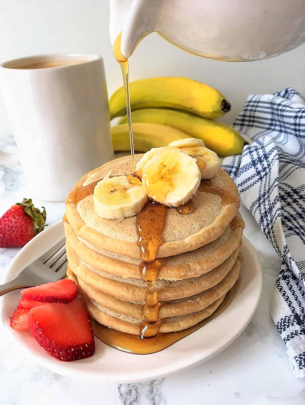 Stack of pancakes on plate with banana and strawberry slices.