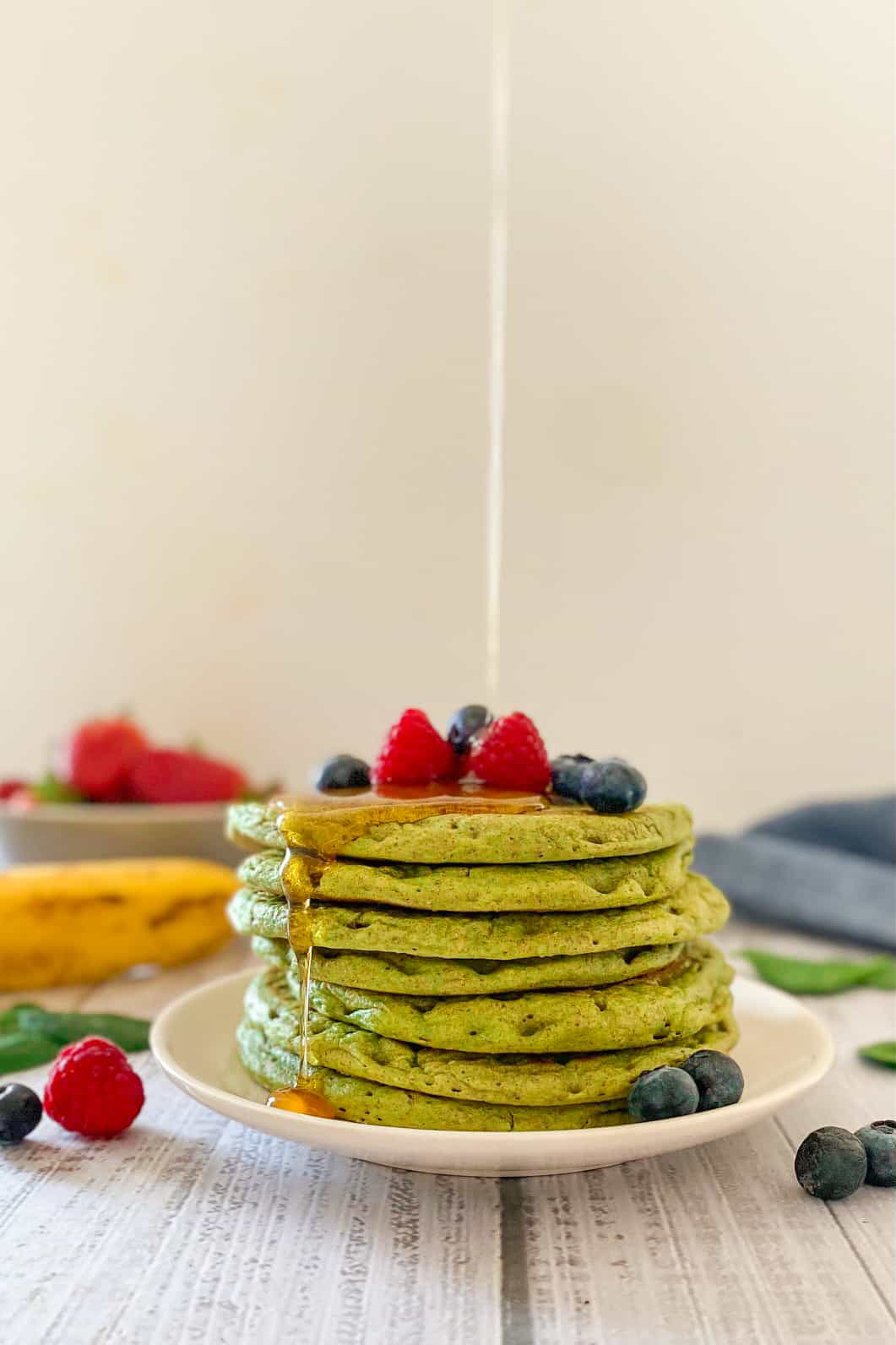 Syrup pouring over stack of green pancakes.