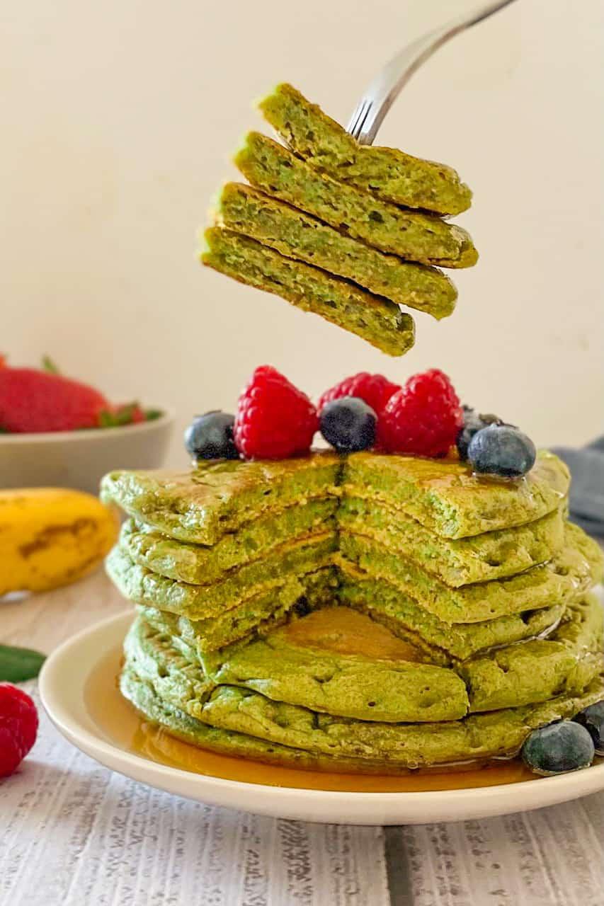 Stack of green pancakes with fork holding up triangular pancake wedge.