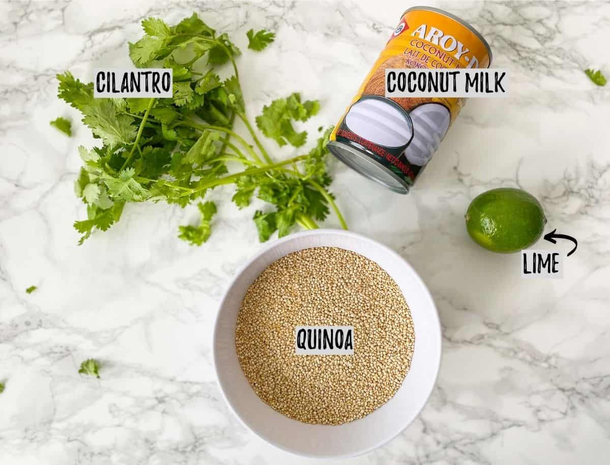 Bowl of raw quinoa, can of coconut milk, lime and cilantro on marble counter.