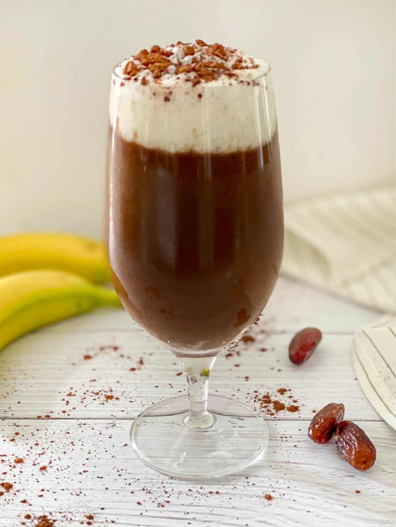 Clear glass with chocolate drink and frothed milk on top with sprinkle of cinnamon.
