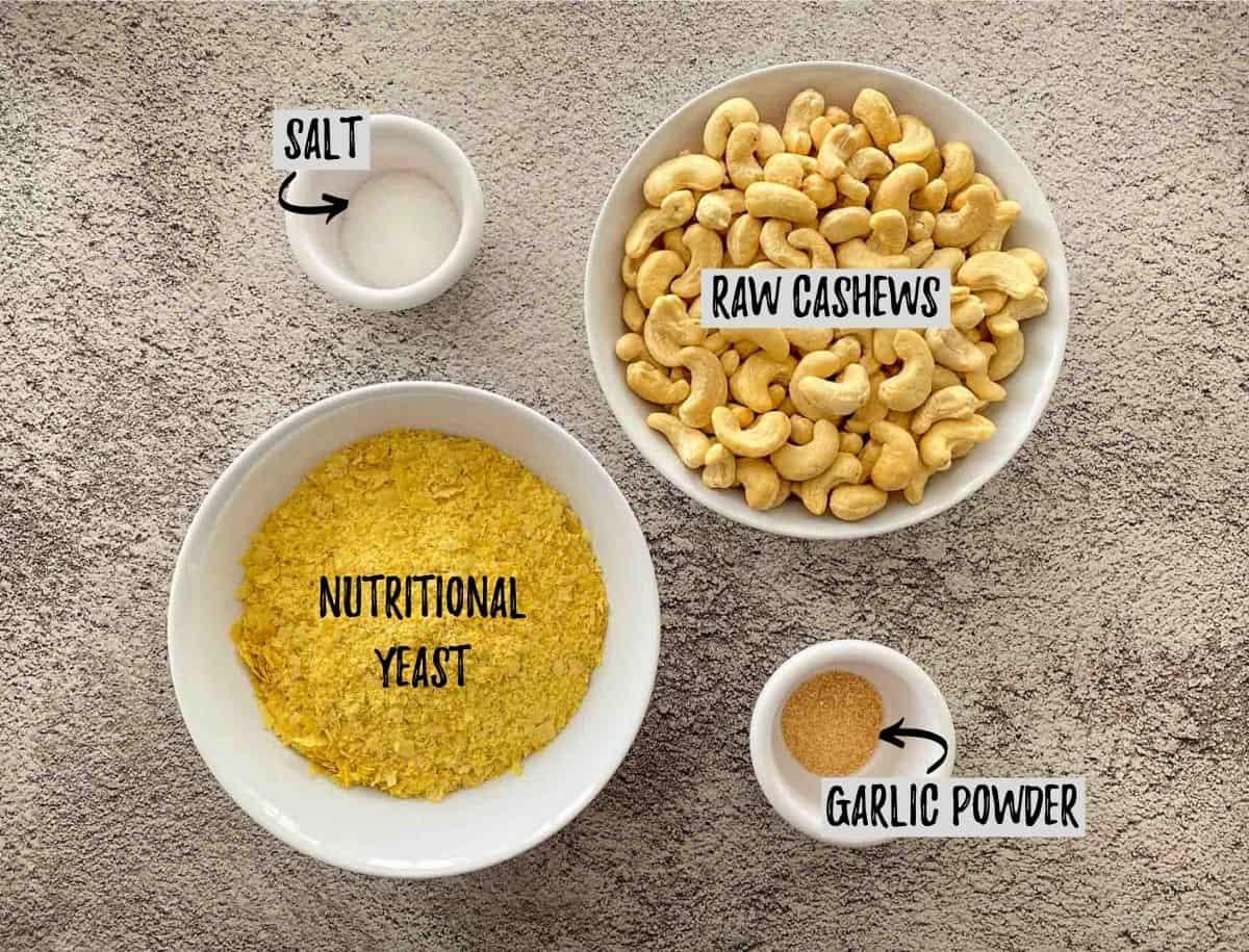 Bowl of cashews, nutritional yeast, salt and garlic powder on concrete deck.