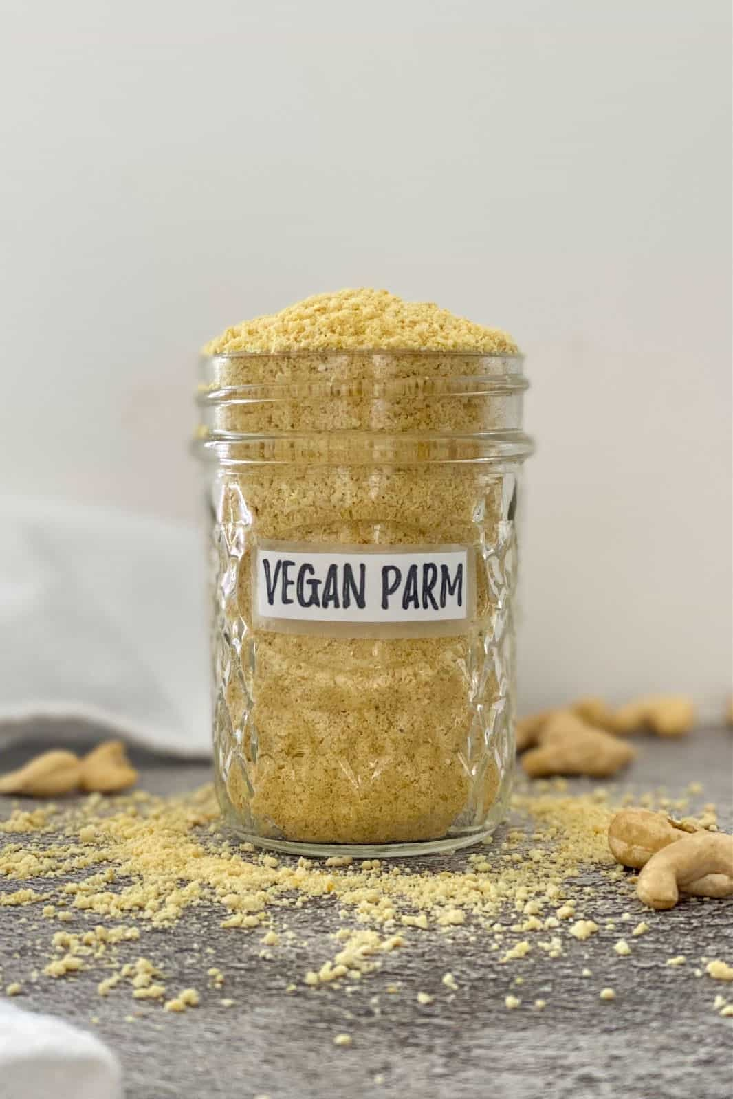 Vegan parmesan cheese overflowing in glass jar with cashews scattered around it.
