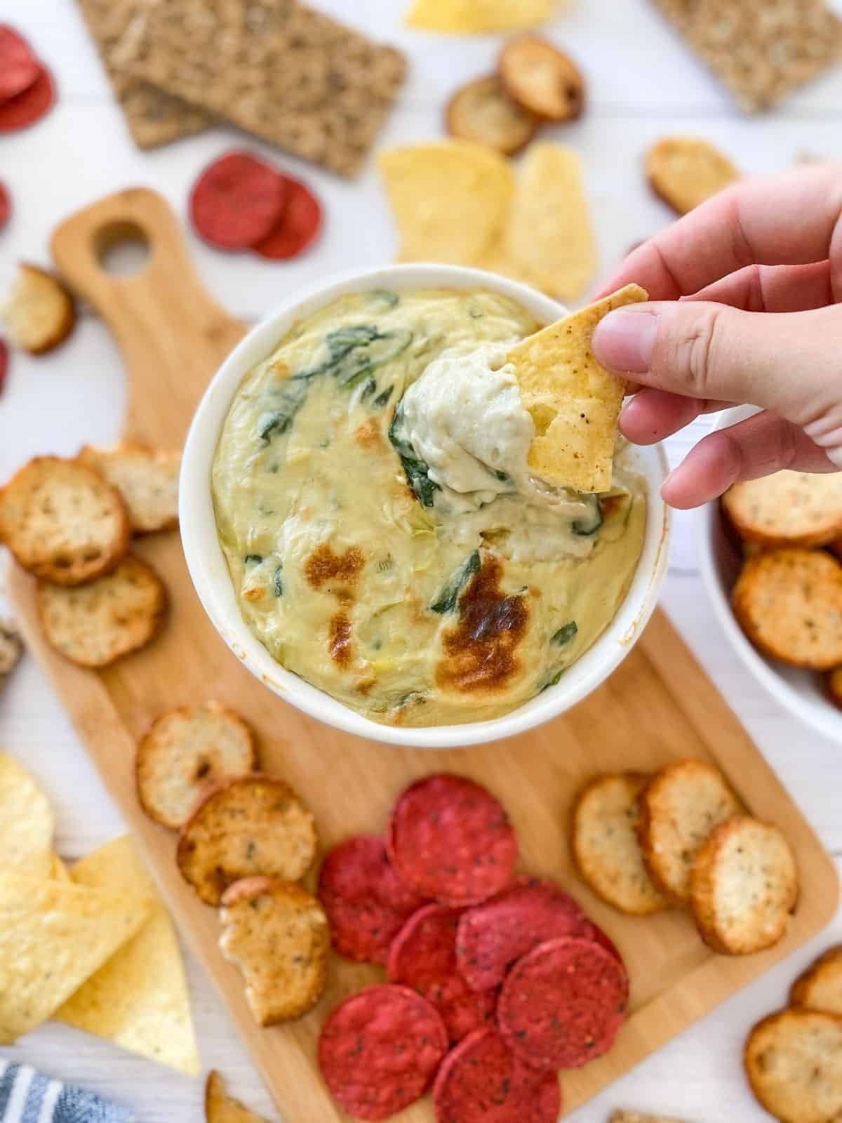 Chip being dunked into bowl of spinach dip.