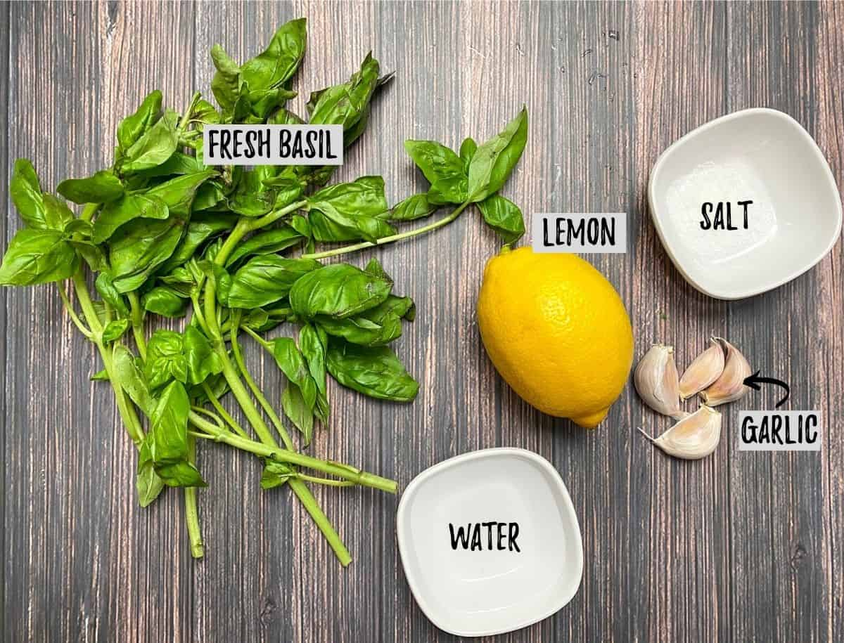 Basil leaves, lemon, garlic cloves and cup of water on brown deck.