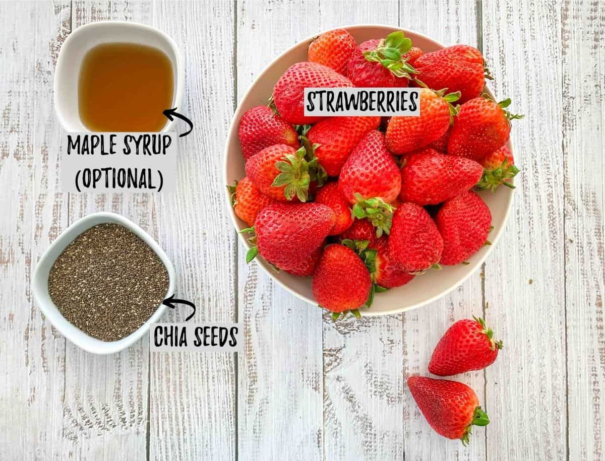 Bowl of ripe strawberries with small bowls of chia seeds and maple syrup beside it.