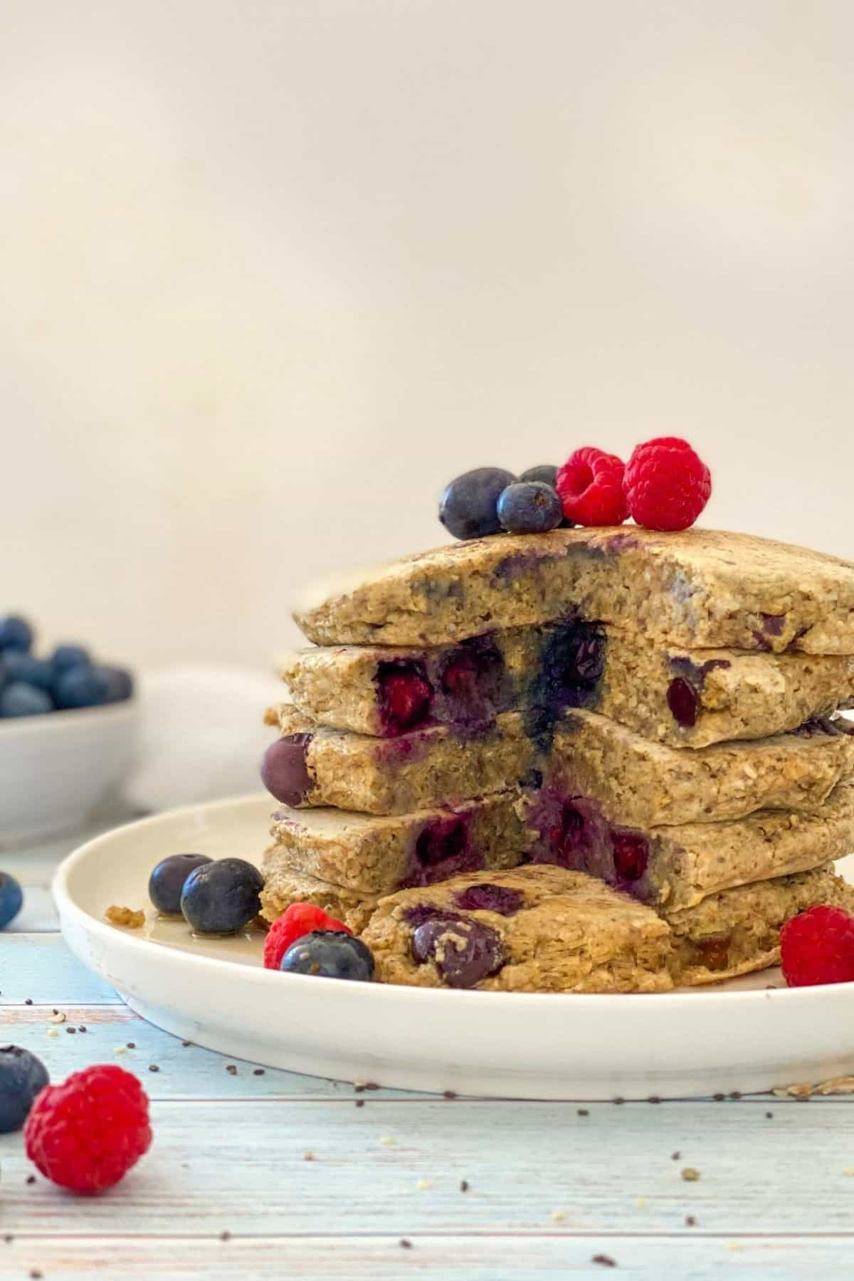 Stack of blueberry pancakes on white plate with triangular wedge cut out through the stack.