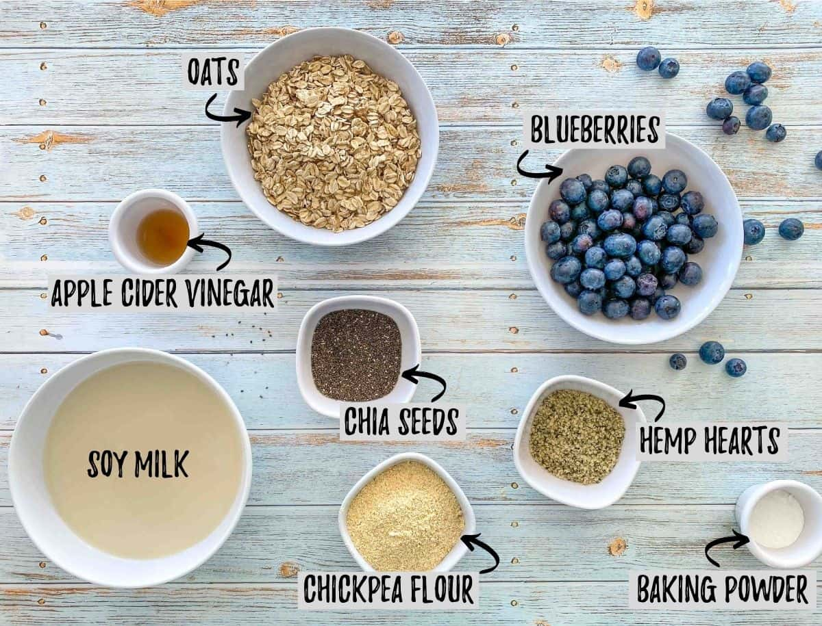 Bowls of oats, milk, blueberries, vinegar, chia seeds, chickpea flour, hemp hearts and baking powder on deck.