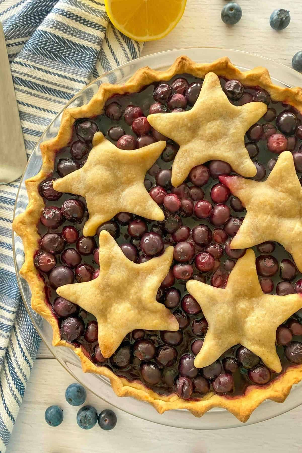 Blueberry pie in pie plate with star shaped pie crust cut outs on top.